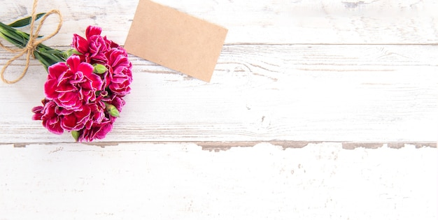 Beautiful carnations with template card isolated on a bright wooden table, copy space, flat lay, top view
