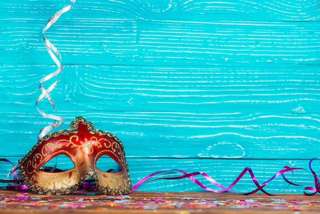 Beautiful carnival mask on blue wooden background