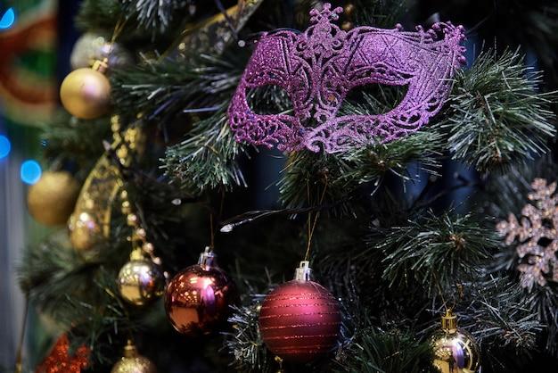 Красивая карнавальная маска висит на елке