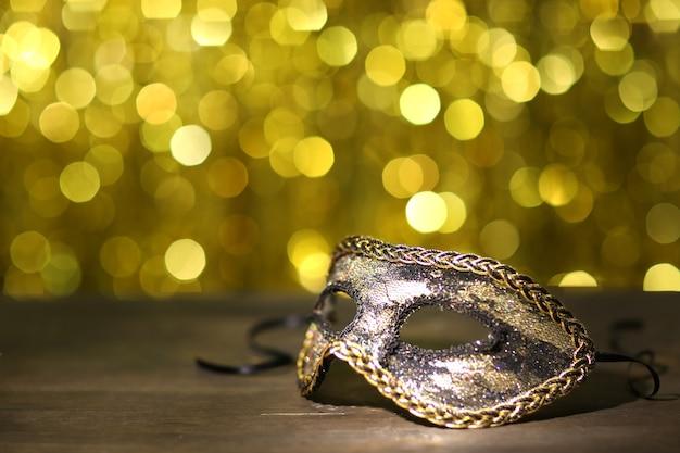 金色の背景のテーブルの上の美しいカーニバルマスク