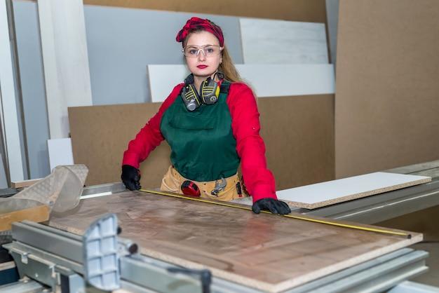 Beautiful carpenter making measurements of wooden plank