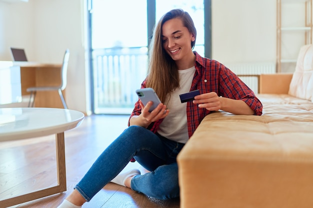 Beautiful casual happy modern young girl using smartphone and credit card for shopping online, paying and ordering goods via the internet