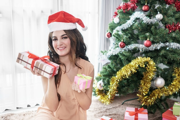 Beautiful casual woman wearing santa's hat sitting while holding