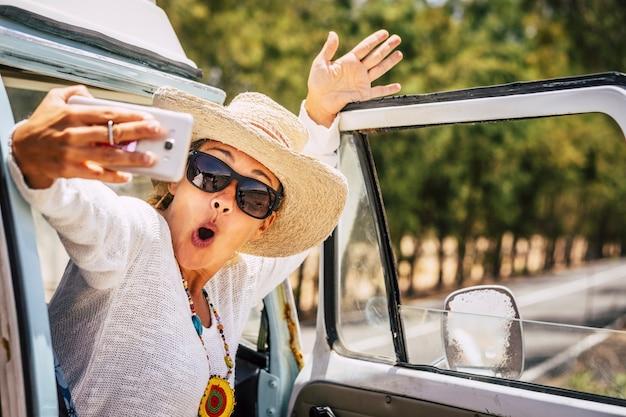 스마트 폰으로 셀카 사진을 찍는 아름다운 백인 성인 여행자 여자