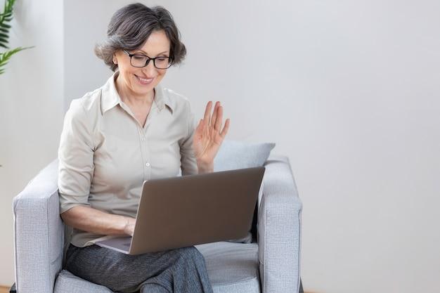 사무실이나 집에 있는 안락의자에 앉아 인터넷을 통해 온라인 통신을 위해 랩톱 컴퓨터를 사용하는 아름다운 백인 여성. 화상 통화, 원격 작업 개념