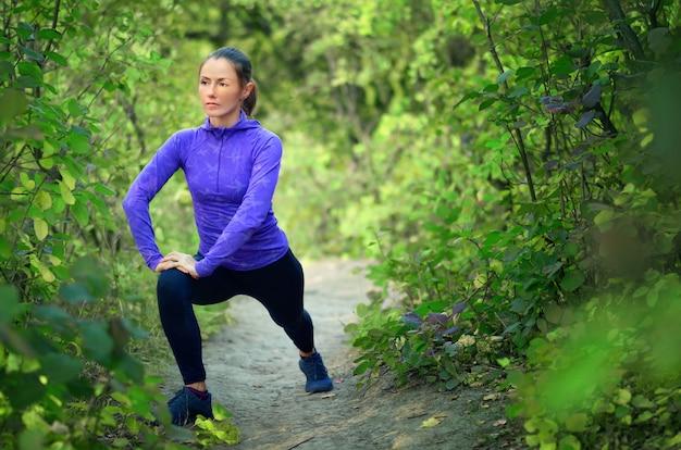 파란색 셔츠와 검은 색 스포츠 레깅스의 아름다운 백인 운동 소녀는 화려한 녹색 숲에 조깅하기 전에 다리로 워밍업을 수행합니다.