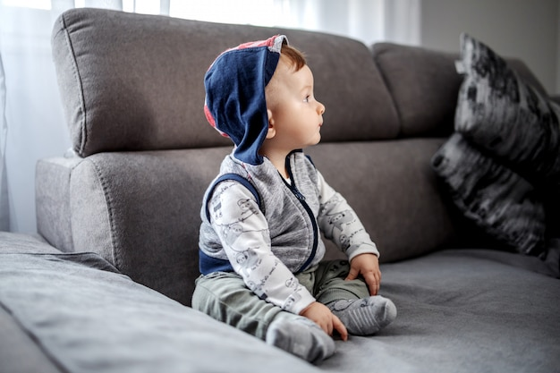 Beautiful caucasian baby boy with hoodie on head sitting on couch in living room and looking away.