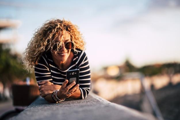 美しい白人の金髪の巻き毛の女性は屋外に横になり、メッセージを送信し、インターネット接続のニュースを読む携帯電話を使用します