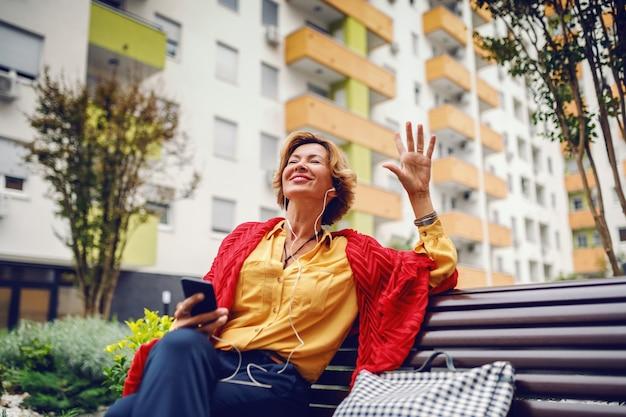 Красивая кавказская белокурая модная старшая женщина сидя на стенде в парке