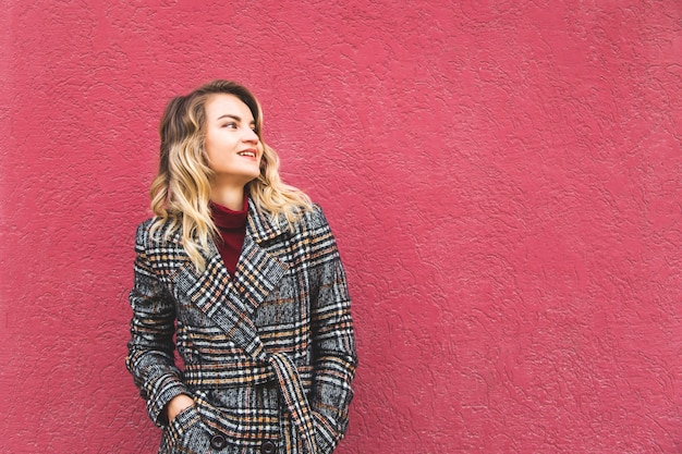 Beautiful caucasian blonde girl in an autumn coat against a bright wall.