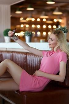 카페에 앉아 스마트폰으로 셀카 사진을 찍는 아름다운 백인 금발 소녀. 소셜 네트워크에서 공유하기 위해 자신의 사진을 찍는 밝은 옷을 입은 소녀.