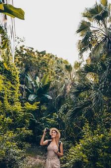 Beautiful caucasian blonde woman asian traveling backpacker tourist woman walking enjoying taking photos in sanya jungle. traveling along asia, active lifestyle concept. discovering hainan, china