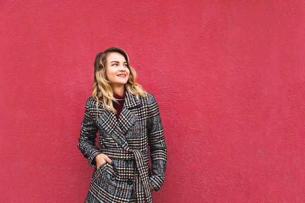 Beautiful caucasian blonde woman in an autumn coat against a bright wall.