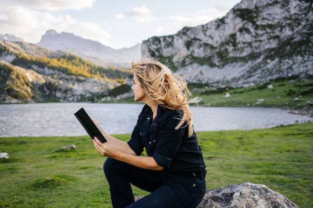 A beautiful caucasian blonde woman reads a book in a mountainous landscape with a lake