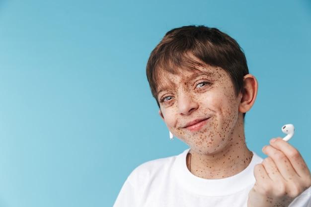Красивый кавказский мальчик с веснушками в белой повседневной футболке и наушниках улыбается изолированно над синей стеной
