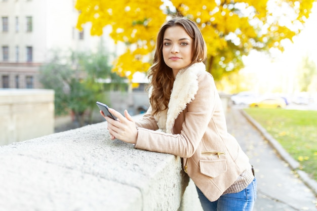Beautiful caucasian brunette girl standing warm autumn day with background of trees with yellow foliage