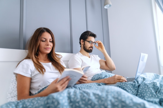 Beautiful caucasian brunette reading book in bed while her husband with eyeglasses using laptop. selective focus on man.