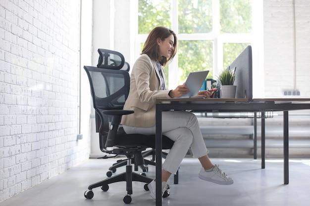 Красивая кавказская бизнес-леди работает с помощью цифрового планшета, сидя в творческом офисе.