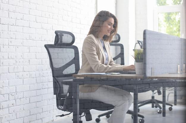 Красивая кавказская бизнес-леди работает, используя ноутбук, сидя в творческом офисе.