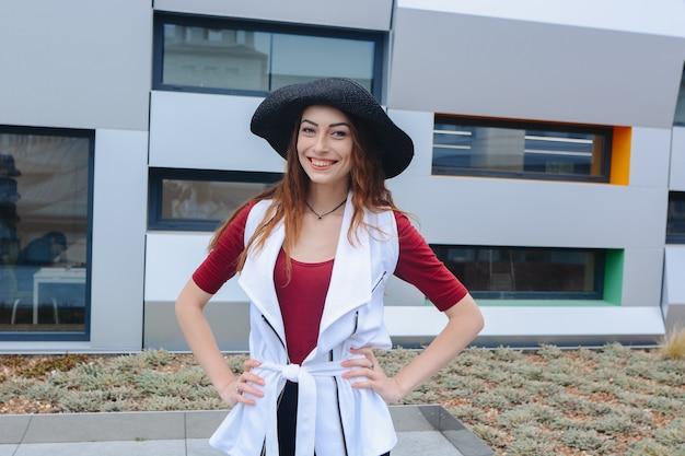 Beautiful caucasian cheerful girl in a hat walks around the city