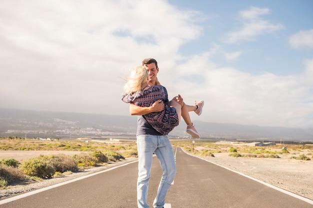 Красивая кавказская пара наслаждается и веселится в летний день. прекрасные люди. мужчина несет блондинку. длинная асфальтированная дорога на заднем плане и пустыня где-нибудь вокруг. голубое небо с облаками
