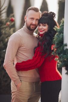 愛の美しい白人カップルがクリスマスイブの路上で一緒に寄り添う