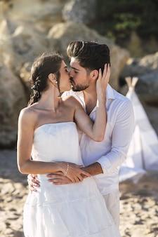 Belle coppie caucasiche che baciano sulla spiaggia