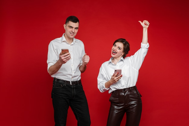 Beautiful caucasian couple in love have a lot of fun and love each other, picture isolated on red wall