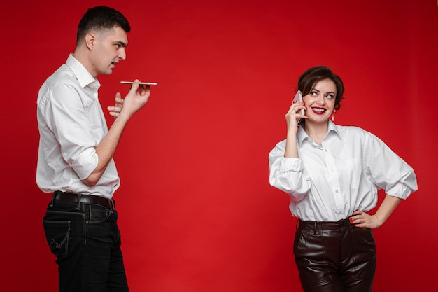 Beautiful caucasian couple in love surfing internet and have a lot of fun, picture isolated on red wall
