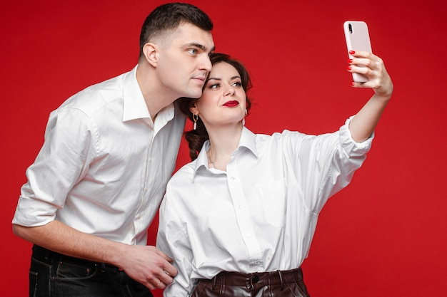 Beautiful caucasian couple in love take selfie and love each other, picture isolated on red wall