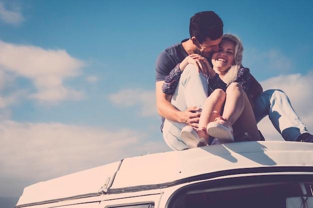 自然なモデルの美しい白人のカップルは、ヴィンテージのキャンピングカーの屋根の上で一緒に関係を維持します。夏の間に旅行する女の子と男の子の若者の間の友情と愛