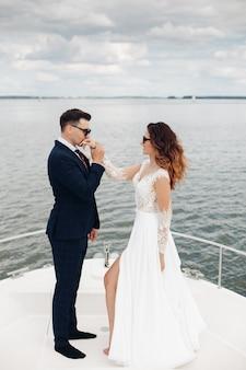 검은 색 선글라스를 쓴 신혼 부부의 아름다운 백인 부부는 하얀 요트에서 신혼 여행을 함께 보내고 거기에서 많은 즐거움을 느낍니다.