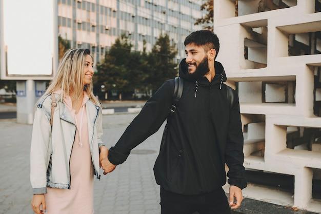 남자가 손을 잡고 도시에 대해 미소 짓는 사랑으로 서로를보고있는 곳을 여행하는 동안 새로운 장소로 여행하는 아름다운 백인 부부.