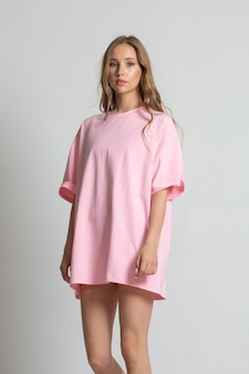 白いスタジオのサイクロラマでポーズをとるピンクのtシャツの美しい白人ダークブロンドの女性