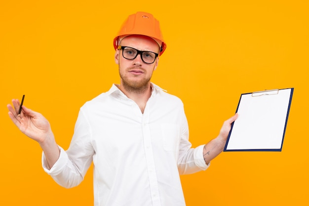 Beautiful caucasian engineer man with glasses and orange helmet isolated on yellow