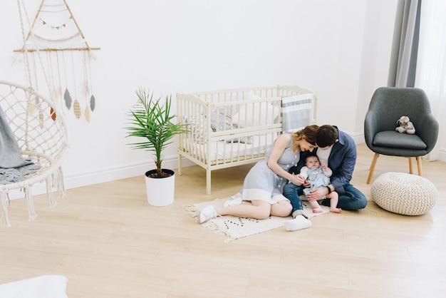Красивая кавказская семья матери, отца и их ребенка из детской комнаты