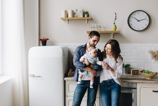 부엌, 어머니, 아버지와 여자 아기의 아름다운 백인 가족
