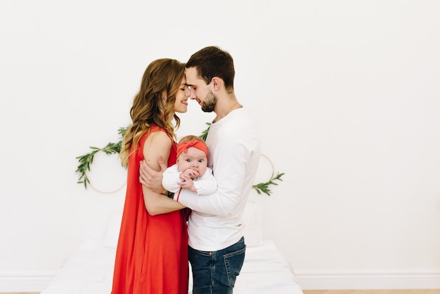 Beautiful caucasian family of three hugging together, father and mother with their baby daughter with space for text