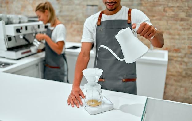 아름다운 백인 여성 바리스타가 커피를 준비하고 매력적인 아프리카 남성 바리스타가 커피를 끓이고, 방법을 붓고, 커피숍에서 커피를 드립합니다.