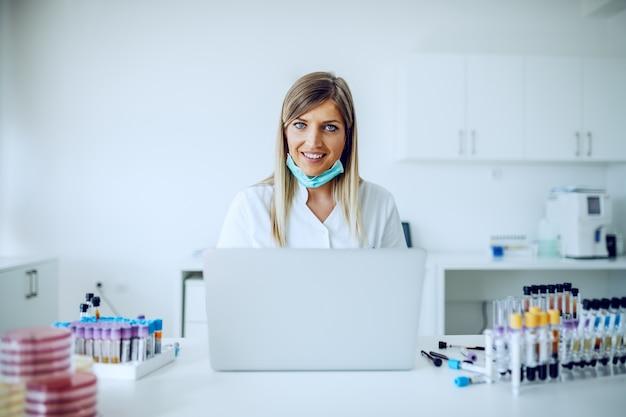 机に座って、データ入力にラップトップを使用して美しい白人女性金髪ラボアシスタント。