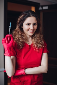 美しい白人女性の美容師は、唇の増強手順の前に注射器を持っています