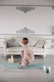 Красивая кавказская женщина медитирует на коврике для йоги возле серого дивана утром