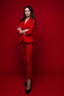 赤いオフィススーツ、黒い靴で長く暗いストレートの髪を持つ美しい白人女性