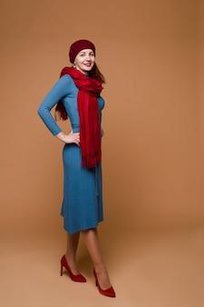 青いドレス、赤い帽子、赤いスカーフのミディアム黒髪の美しい白人女性
