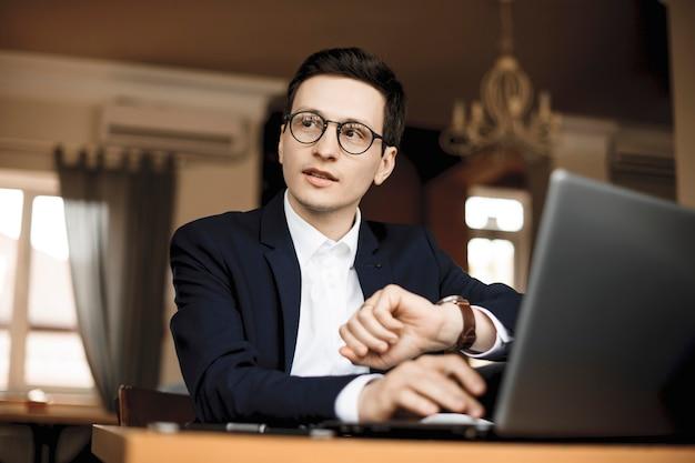 彼の机に座って彼の時計を見ながら誰かと話している美しい白人のフリーランサー。
