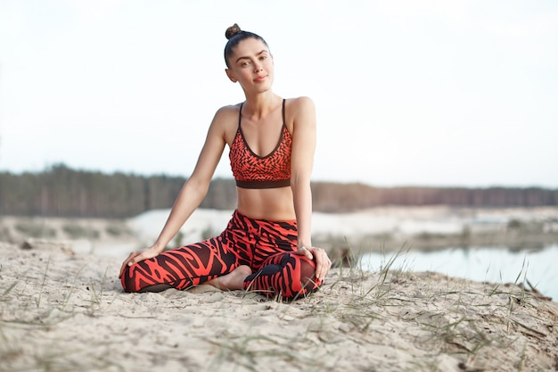 A beautiful caucasian girl in a bright red sportswear do yoga position stretching on nature