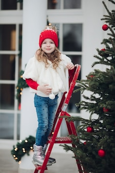 Beautiful caucasian girl decorates large christmas tree with help of ladder outside