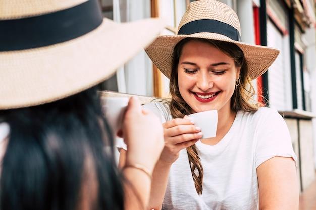 美しい白人の女の子がバーで彼女の友人とイタリアのエスプレッソコーヒーを飲みます