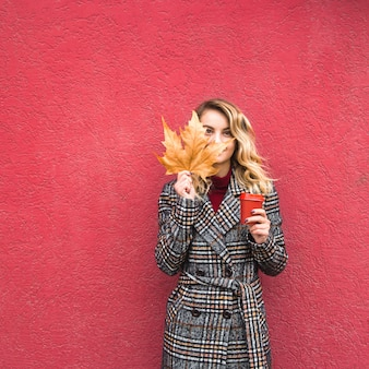 Beautiful caucasian girl holding a yellow autumn leaf and a red cup of coffee