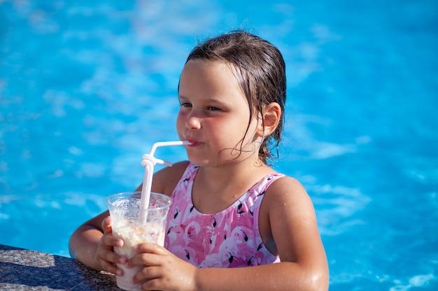 Красивая кавказская девушка в розовом купальнике наслаждается питьем молочного коктейля из соломинки в бассейне